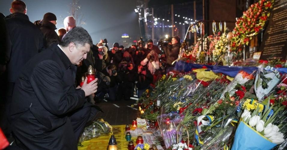20.fev.2015 - O presidente ucraniano, Petro Poroshenko, coloca uma vela em frente ao memorial em homenagem aos mortos durante onda de protestos conhecida como Euromaidan, que exigia a aproximação da Ucrânia à Europa e há um ano resultou na queda do presidente pró-Rússia Viktor Yanukovich. As autoridades ucranianas declararam 20 de fevereiro como 'Dia dos Heróis da Centena Celestial', como são conhecidos na Ucrânia os mortos nos confrontos que começaram após três meses de intensas manifestações
