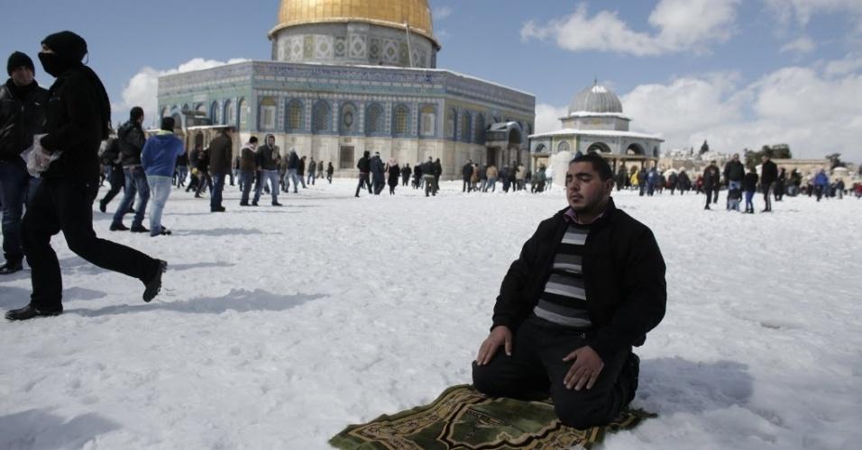 20.fev.2015 - Palestino reza do lado de fora da mesquita Rock de Al Aqsa, o terceiro local mais sagrado do Islã, após uma tempestade de neve em Jerusalém, em Israel. A cidade acumulou 25 centímetros de neve entre quinta e sexta-feira