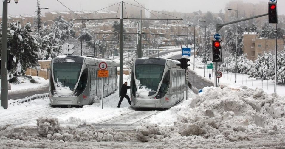 20.fev.2015 - Pedestres passam por trens parados por conta do acúmulo de neve em Jerusalém, em Israel. A cidade acumulou 25 centímetros de neve entre quinta e sexta-feira