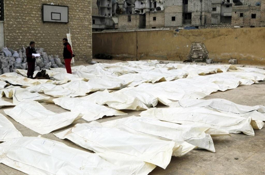 23.fev.2015 - Corpos de membros das forças leais ao ditador da Síria, Bashar Assad, são separados antes de serem enterrados em Aleppo, nesta segunda-feira (23). Os rebeldes disseram que os soldados foram mortos durante os confrontos na região de Al Mallah, enquanto tentavam cercar o local e bloquear as linhas de abastecimento dos insurgentes