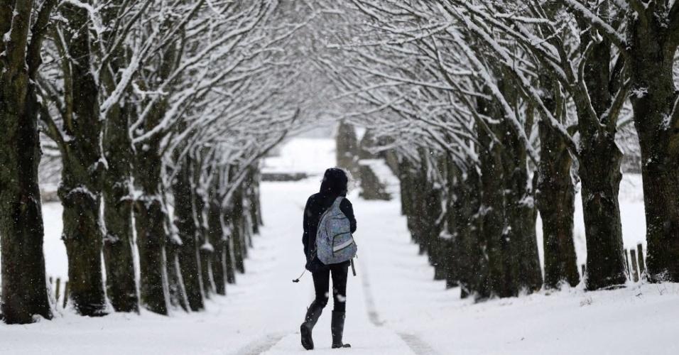 23.fev.2015 - Estudante caminha ao longo de uma estrada coberta  por neve em Moulin, na região central da Escócia, nesta segunda-feira (23)