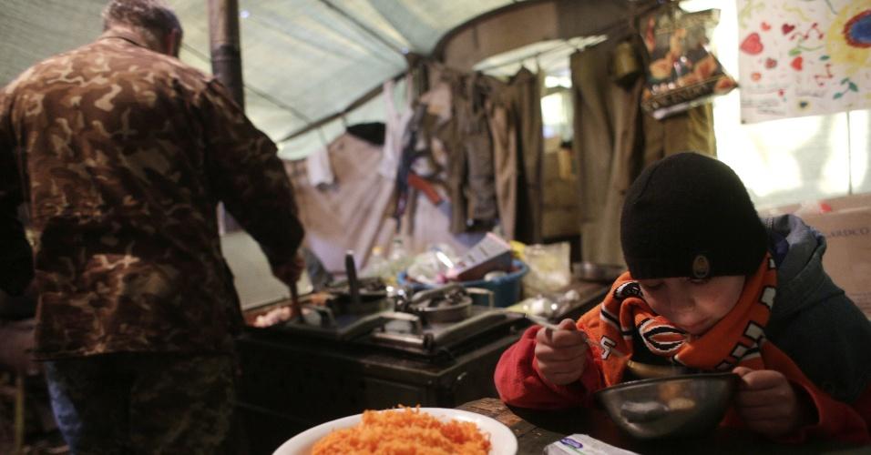 23.fev.2015 - Um soldado ucraniano alimenta um menino em um posto de controle perto Horlivka, na região de Donetsk. As forças pró-Rússia se concentraram nas proximidades da cidade portuária da Ucrânia de Mariupol e continuam a atacar posições de tropas do governo ucraniano, alimentando preocupações com o destino de um cessar-fogo mediado internacionalmente