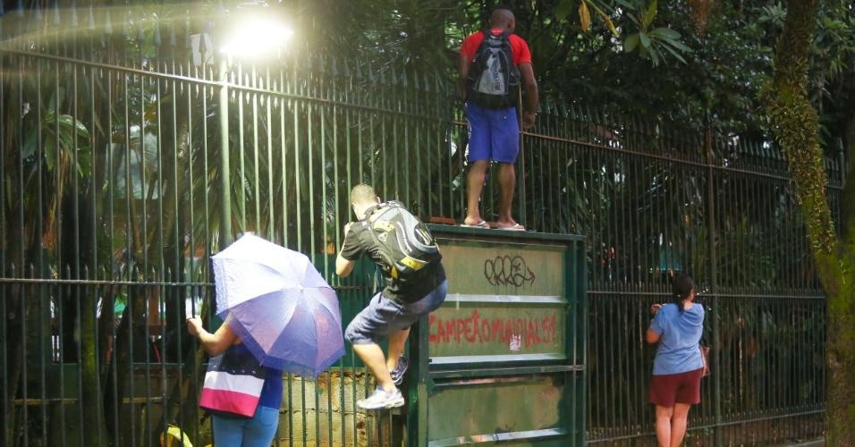 25.fev.2015 - Pedestres sobem nas grades do Allianz Parque para escapar do alagamento na rua Turiasu com avenida Sumaré, na zona Oeste da capital paulista, durante tarde desta quarta-feira (25) por causa das fortes chuvas