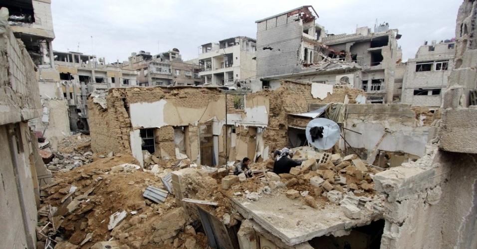 25.fev.2015 - Moradores procuram por pertences em meio aos escombros de suas casas no bairro de Douma, da capital Damasco, na Síria. A foto foi tirada em 24 de fevereiro