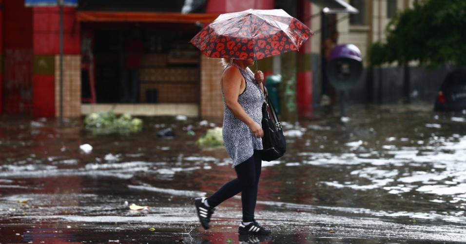 25.fev.2015 - Pedestre caminha em rua alagada no centro de São Paulo fica durante as fortes chuvas atingem a capital paulista na tarde desta quarta-feira (25)