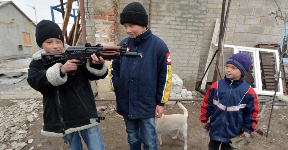 26.fev.2015 - Crianças brincam com uma submetralhadora dada por soldados ucranianos no vilarejo de Chermalyk, a 40 quilômetros do porto de Mariupol, no leste do país
