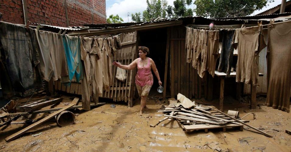 27.fev.2015 - Moradora de Cobija, na fronteira boliviana com o Brasil, observa roupas sujas de barro estendidas no varal, após alagamento na cidade, nessa sexta-feira (27). Mais de 2.000 pessoas ficaram sem casa ao longo da fronteira depois que chuvas elevaram o nível dos rios Acre e Tahuamanu, que vazaram de seus leitos e invadiram as cidades de Cobija e Pando, na Bolívia, e Brasileia, no Acre