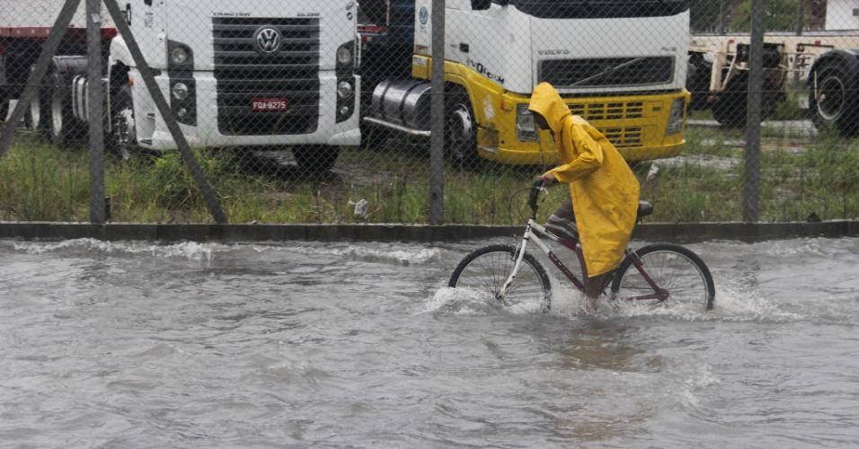 28.fev.2015 - Ciclista enfrenta ponto de alagamento na avenida Nossa Senhora de Fátima, região noroeste de Santos, no litoral de São Paulo, na manhã deste sábado (28), após fortes chuvas na cidade