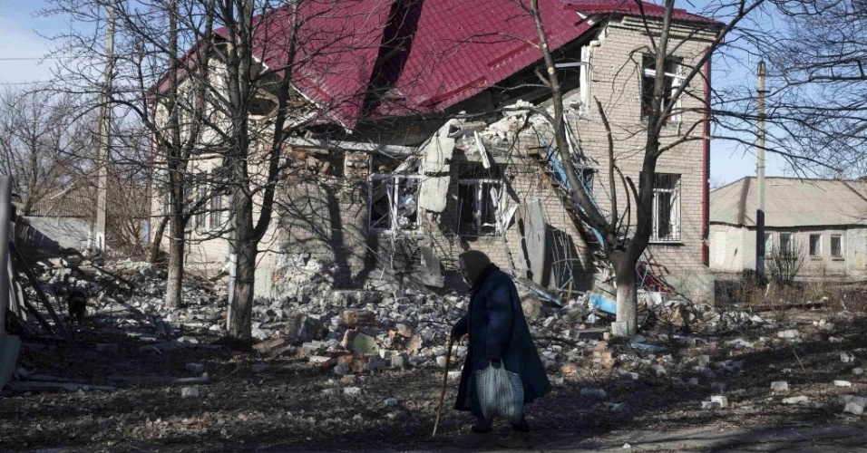 28.fev.2015 - Idosa caminha na frente de uma casa na cidade de Debaltseve, na Ucrânia, destruída pelo conflito entre o Exército nacional e rebeldes separatistas pró-Rússia. A cidade está sob domínio dos rebeldes