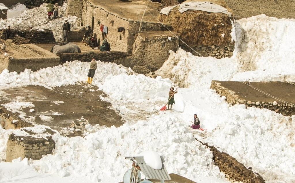 28.fev.2015 - Moradores retiram neve dos telhados das casas depois de uma avalanche, no distrito de Paryan, na província de Panjshir, no Afeganistão. De acordo com as autoridades locais, as equipes de resgate reiniciaram as operações de busca de vítimas. Quase 200 pessoas morreram no desastre natural