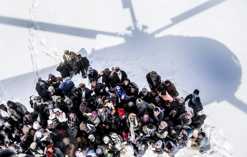 28.fev.2015 - Sobreviventes de uma avalanche esperam para receber alimentos e materiais de socorro distribuídos por um helicóptero do Exército, no distrito de Paryan, na província de Panjshir, no Afeganistão. De acordo com as autoridades locais, as equipes de resgate reiniciaram as operações de busca de vítimas. Quase 200 pessoas morreram no desastre natural