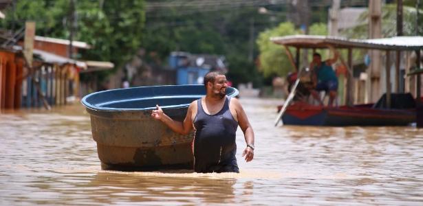 Morador arrasta caixa de água em rua completamente alagada da capital acriana