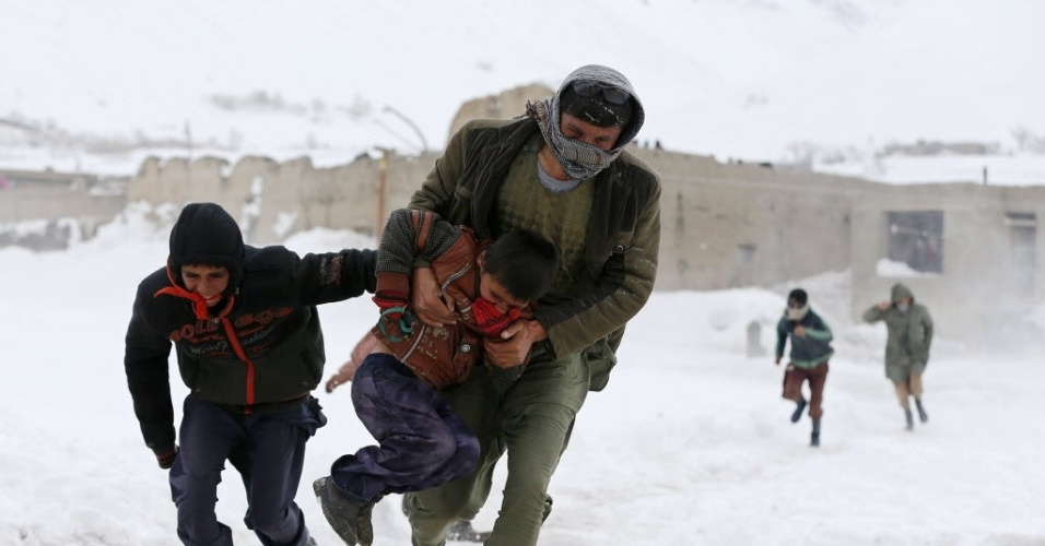 2.mar.2015 - Afegãos sobreviventes de uma avalanche correm para pegar mantimentos distribuídos pelo exército na província de Panjshir, ao norte do país. Mais de 180 pessoas morreram em decorrência da pior avalanche dos últimos 30 anos