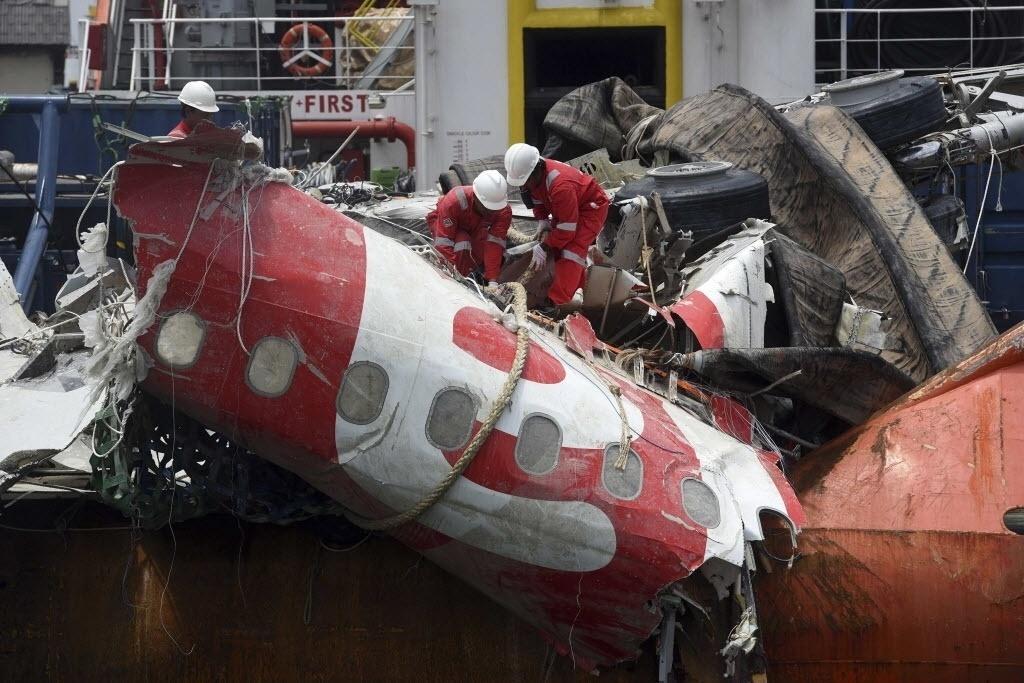 2.mar.2015 - Funcionários do governo da Indonésia removem a fuselagem do avião da AirAsia de uma embarcação no porto de Tanjung Priok, em Jacarta. O país recuperou a última grande parte do avião, do voo QZ8501, que caiu no mar de Java em dezembro, matando todas as 162 pessoas a bordo