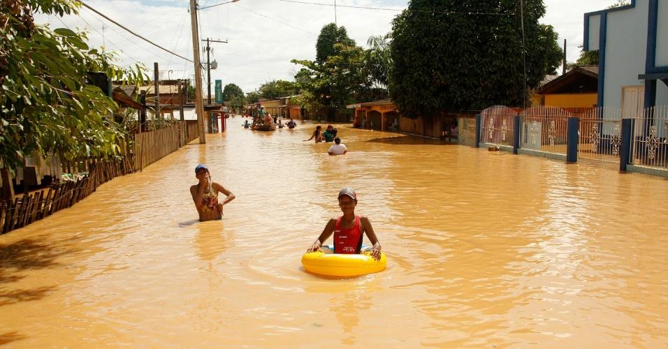 2.mar.2015 - Pessoas se deslocam com boias e canoas, em Rio Branco, no Acre