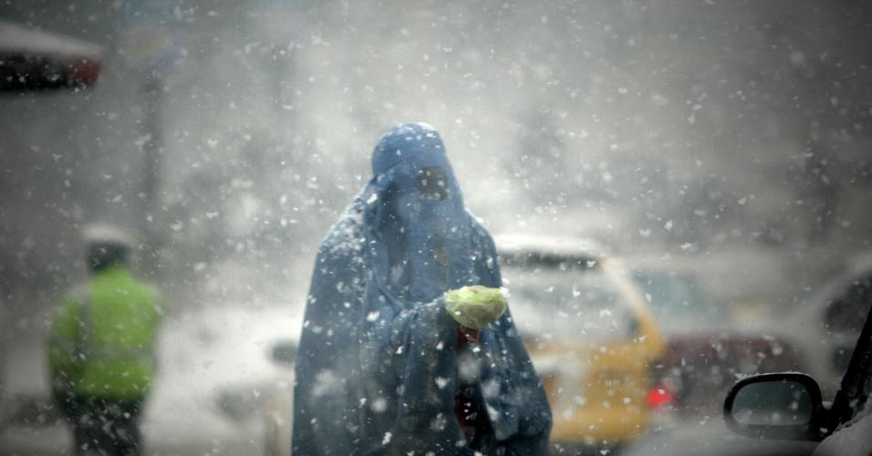 Mulher vestida com burca caminha sob uma tempestade de neve nesta quarta-feira (4), em Cabul, no Afeganistão