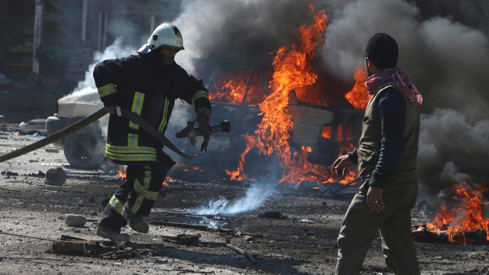 5.mar.2015 - Bombeiros tentam apagar as chamas de um carro atingido por uma bomba em ataque feito por forças leais ao presidente sírio, Bashar al-Assad, no bairro de Qadi Askar, em Aleppo, na Síria, nesta quinta-feira (5)