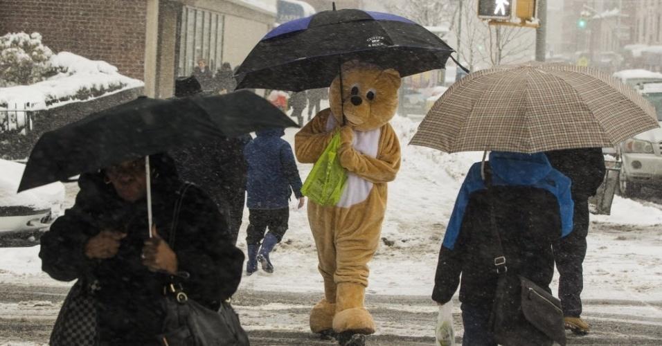 5.mar.2015 - Pedestre usando fantasia de animal se protege da neve com guarda-chuva em Nova York. O Serviço Nacional de Meteorologia emitiu um alerta de nevasca para Nova York, com os meteorologistas prevendo que o acúmulo de neve possa superar os dois metros na cidade