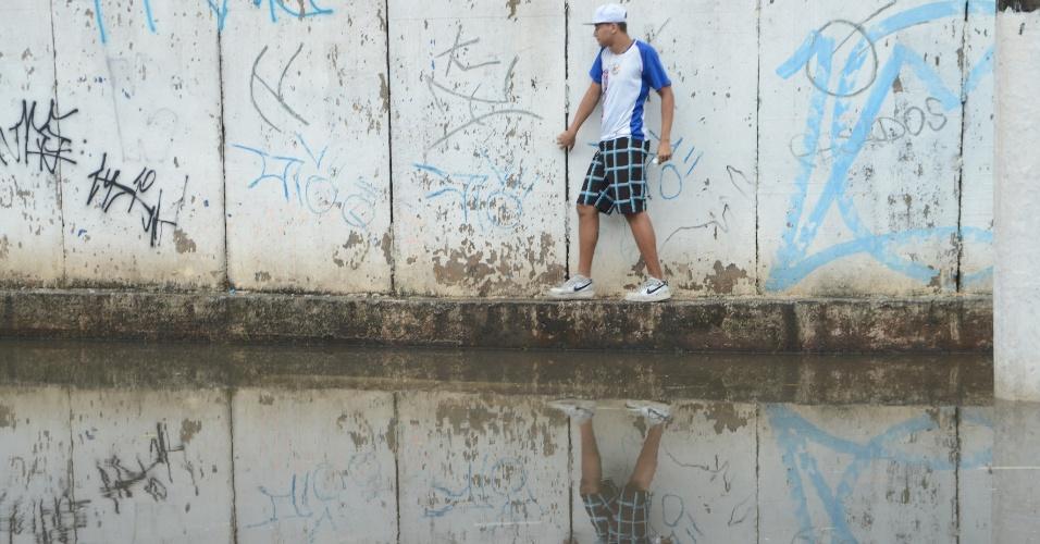 7.mar.2015 - A chuva forte na tarde deste sábado (7) provocou pontos de alagamentos em algumas regiões de São Paulo. Nesta foto, o rapaz se equilibra para passar por um trecho no bairro Rochdale, no município de Osasco, na região metropolitana
