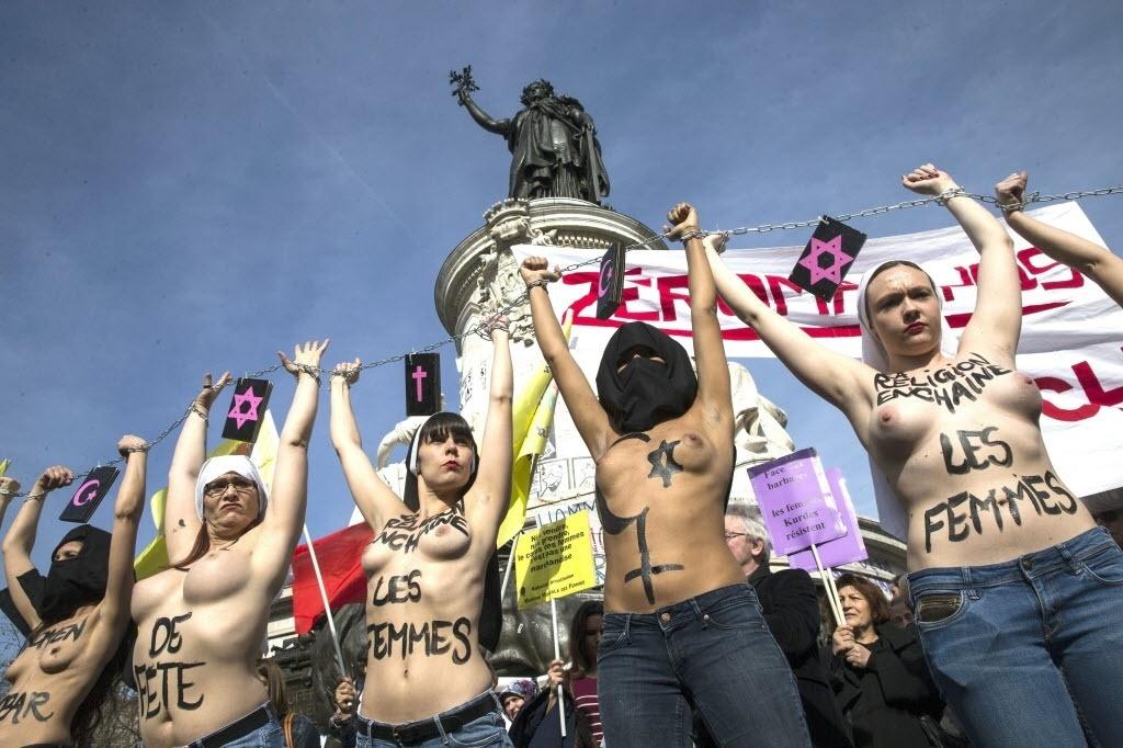 8.mar.2015 - Ativistas do Femen (grupo feminista famoso pelos atos em que utilizam topless) se acorrentam na Praça da República, em Paris, em protesto no Dia Internacional das Mulheres, neste domingo (8)