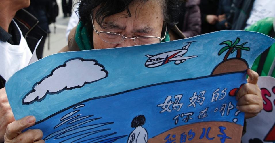 8.mar.2015 - Mãe de um dos passageiros do voo MH370 da Malaysia Airlines chora durante reunião de membros das famílias dos desaparecidos. O Boeing 777 levava 239 pessoas a bordo e sumiu enquanto voava de Kuala Lumpur para Pequim no dia 8 de março de 2014