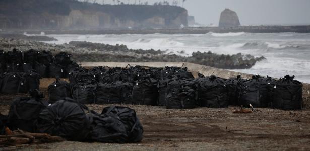 Sacos plásticos contendo terra, folhas e destroços contaminados são colocados perto do mar, na cidade de Tomioka, região de Fukushima, perto da usina nuclear. A foto é de março de 2015