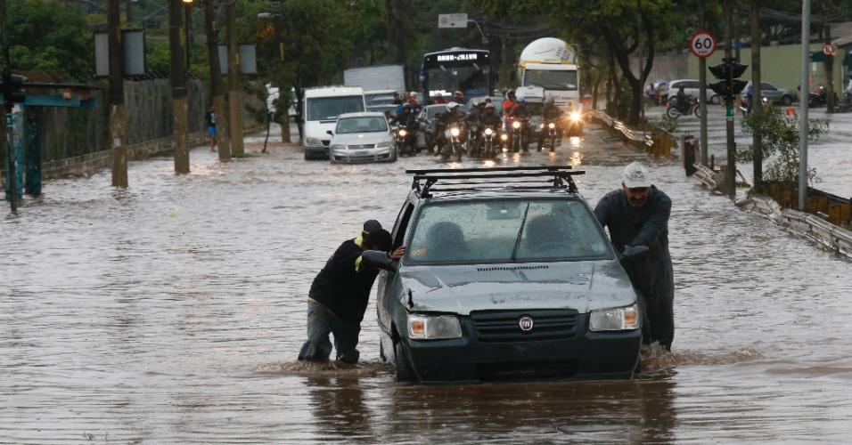 16.mar.2015 - Homens arrastam um carro em um ponto de alagamento na avenida Almirante Delamare, próximo à divisa com São Caetano (SP), durante forte chuva que caiu na tarde desta segunda-feira (16) em São Paulo