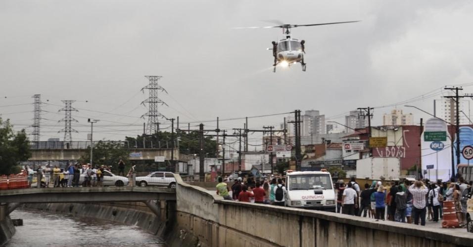 19.mar.2015 - Com ajuda de helicóptero, bombeiros procuram por homem que caiu no rio Aricanduva, na zona leste de São Paulo, ao tentar salvar um cão durante o temporal da tarde testa quinta-feira (19)