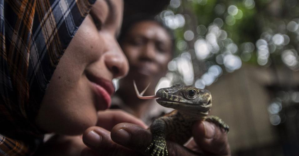 19.mar.2015 - Mulher segura filhote de dragão de komodo em zoológico da Ilha de Java. O pequeno animal tem duas semanas de vida, e nasceu após ser chocado em incubadora