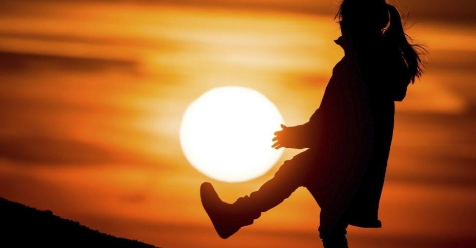 19.mar.2015 - Uma menina parece segurar o sol com as mãos preparando-se para chutá-lo, como se ele fosse uma bola. Apenas um entardecer em Sieversdorf, na Alemanha