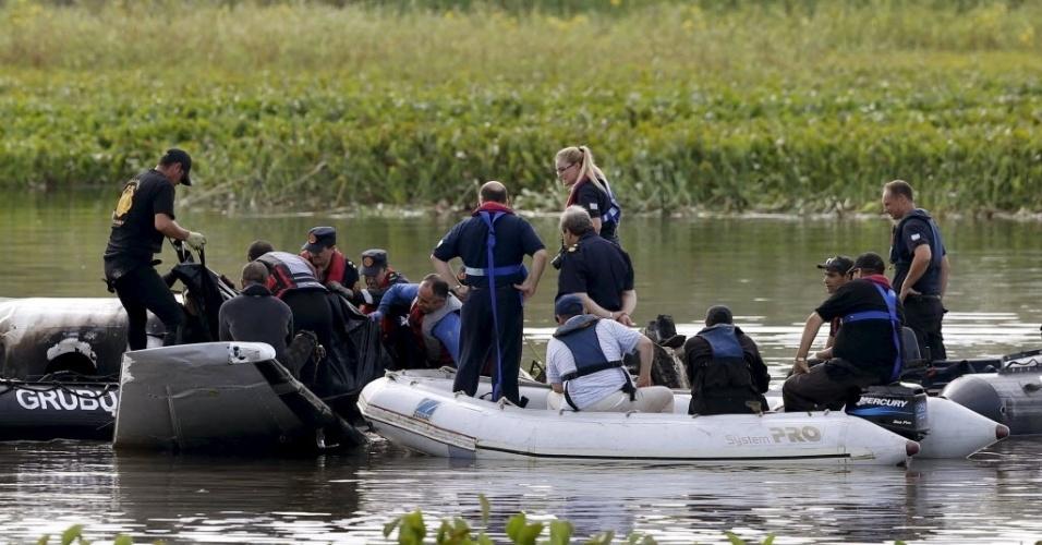20.mar.2015 - Equipe de resgate retira corpo de vítima dos destroços de um avião argentino que caiu na Laguna del Sauce, perto da cidade de Punta del Este, no Uruguai. A aeronave transportava oito passageiros e dois tripulantes e não há nenhum sobrevivente, de acordo com um porta-voz da Força Aérea uruguaia