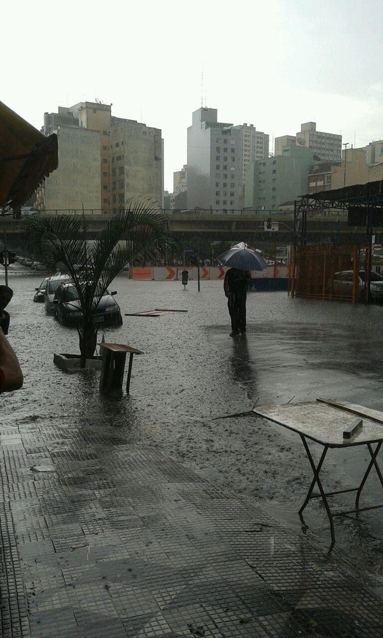 20.mar.2015 - Da rua Helvétia, pedestre observar cruzamento alagado na avenida São João, no centro de São Paulo,na tarde desta sexta-feira (20)