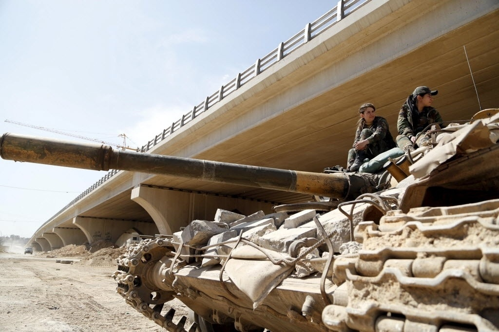 20.mar.2015 - Soldados mulheres do Comando Batalhão, que faz parte do Exército sírio, sentam em cima de um tanque em Jobar, subúrbio de Damasco. Este batalhão é composto por centenas de mulheres que passaram por treinamento militar. Foto foi tirada em 19 de março durante uma viagem organizada pelo Exército da Síria