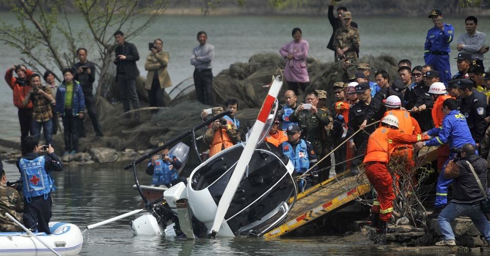 22.mar.2015 - Bombeiros resgatam os destroços de um pequeno helicóptero que caiu num lago na cidade de Hefei, na China, na sexta-feira. A aeronave tinha dois ocupantes. O passageiro ficou ferido e o piloto continua desaparecido