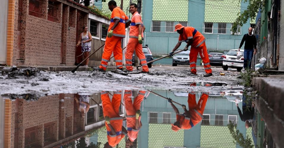 23.mar.2015 - Garis limpam lama acumulada em consequência da forte chuva de domingo (22) na rua Miguel Burner, em Bonsucesso, no Rio de Janeiro