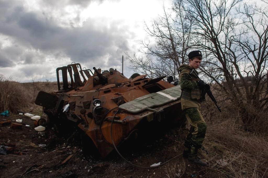 23.mar.2015 - Rebelde pró-Rússia passa por tanque ucraniano destruído perto da cidade de Metalist. A Ucrânia acusou os separatistas de disparar foguetes contra soldados e violar o cessar-fogo
