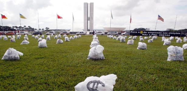 Ato com 200 sacos que representam dinheiro cobra reforma política, em frente ao Congresso Nacional, em Brasília