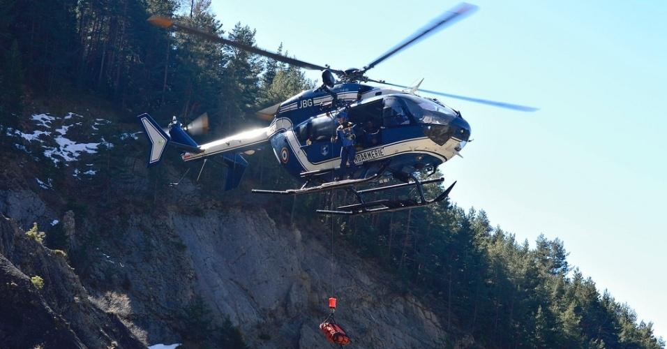 26.mar.2015 - Helicóptero da equipe de resgate retira restos mortais do local do acidente do voo 4U9525, da companhia aérea Germanwings, perto de Seyne-les-Alpes, na França. O grupo de técnicos e alpinistas está mapeando a área e coletando pertences e partes do avião para identificação