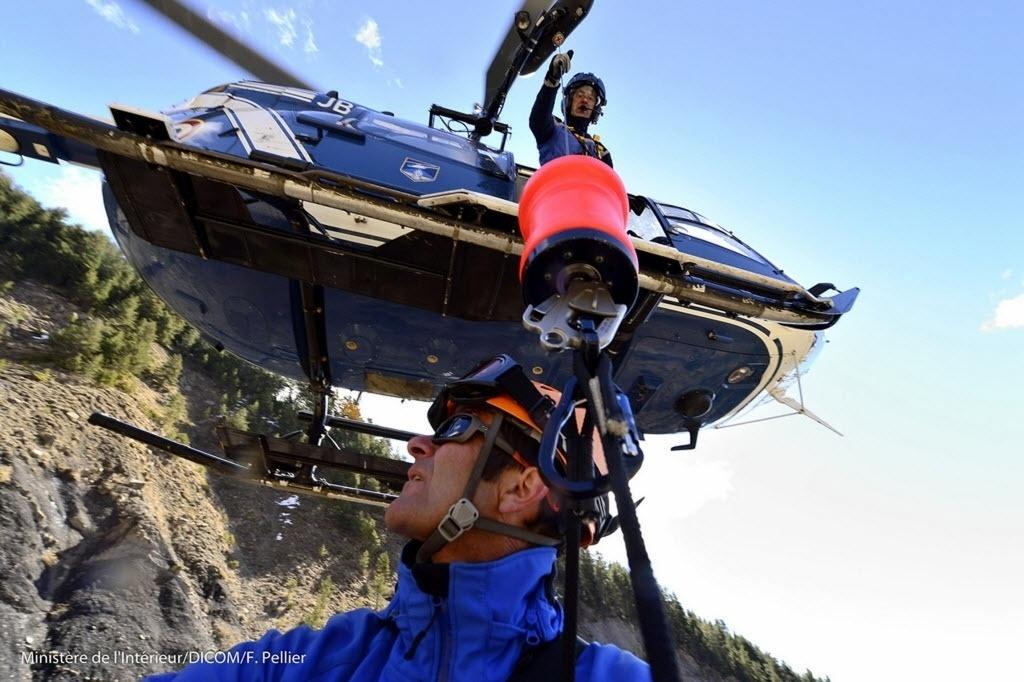 27.mar.2015 - Técnico da equipe de resgate é içado de helicóptero para o local do acidente do Airbus A320 da Germanwings,a França. Os áudios da primeira caixa preta mostraram que a queda foi intencional por parte do copiloto da aeronave, Andreas Lubitz, que se trancou na cabine quando o piloto saiu para ir ao banheiro. Nenhum corpo foi encontrado intacto