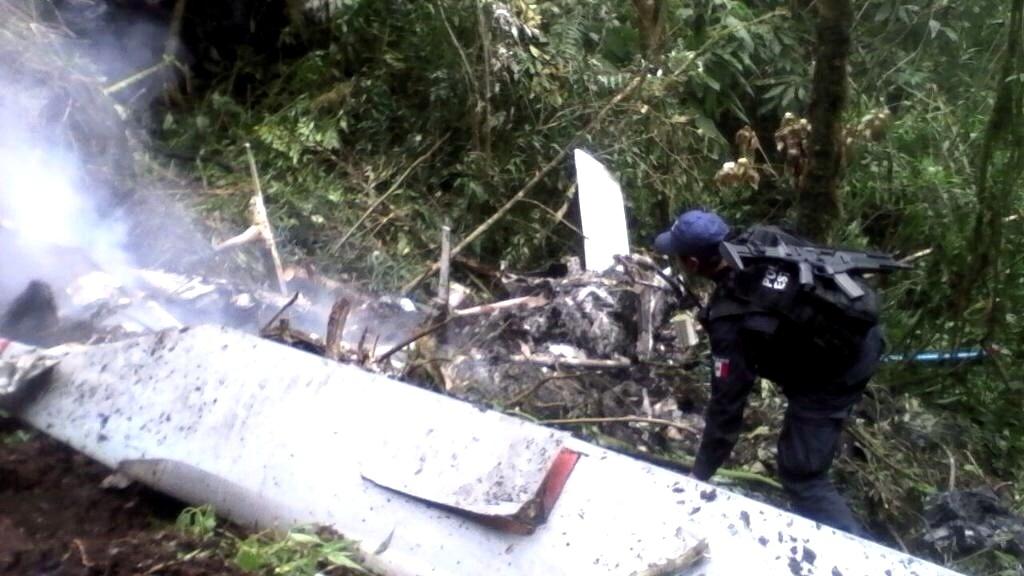 28.mar.2015 - Equipe de segurança inspeciona local do acidente de um helicóptero na cidade mexicana de San Martin de Porres, no sul do país, na noite desta sexta-feira (27). As quatro a bordo do aparelho, da companhia TelMex morreram no acidente