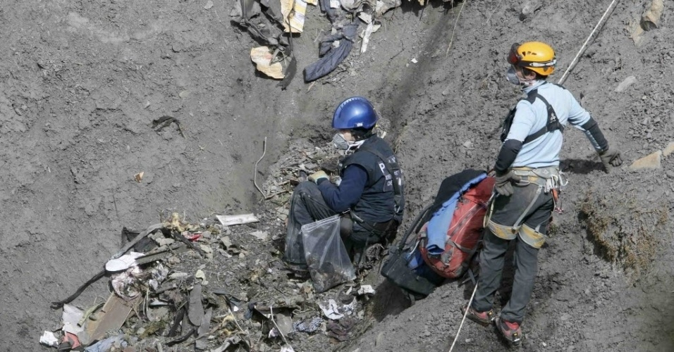 29.mar.2015 - Investigador francês inspeciona os destroços do avião da Germanwings que caiu nos Alpes franceses na terça-feira (24). A cadência de voos de helicóptero no local da tragédia diminuiu depois de a polícia conseguir isolar a área, o que facilitou os trabalhos dos investigadores