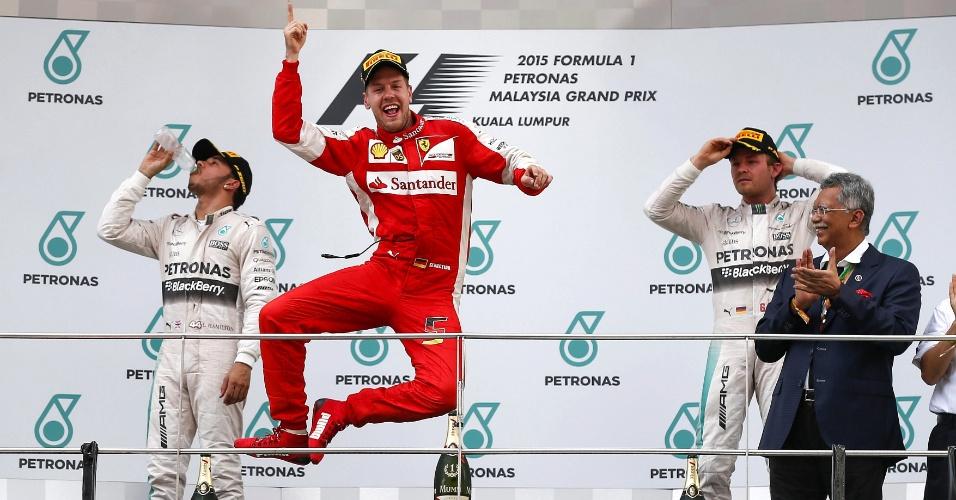 29.mar.2015 - O piloto alemão da Fórmula 1 Sebastian Vettel, da Ferrari, comemora no pódio a vitória no Grande Prêmio da Malásia, em Sepang, neste domingo (29). Lewis Hamilton, à esquerda, e Nico Rosberg, ambos da Mercedes, ficaram em segundo e terceiro lugar, respectivamente. A Ferrari não vencia um GP de Fórmula-1 desde maio de 2013