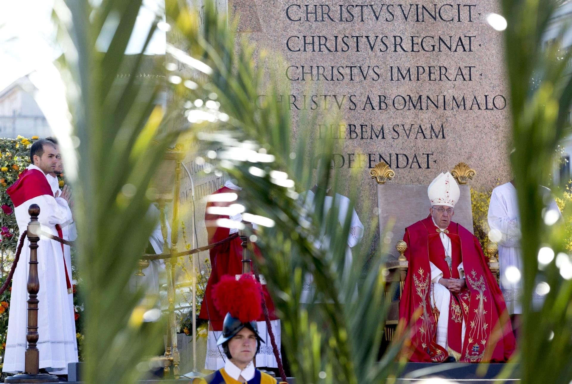 29.mar.2015 - Parcialmente encoberto por ramos de palmeiras, o papa Francisco conduz missa em celebração do domingo de Ramos na praça São Pedro, no Vaticano, neste domingo (29). A data marca para os católicos o início da Semana Santa