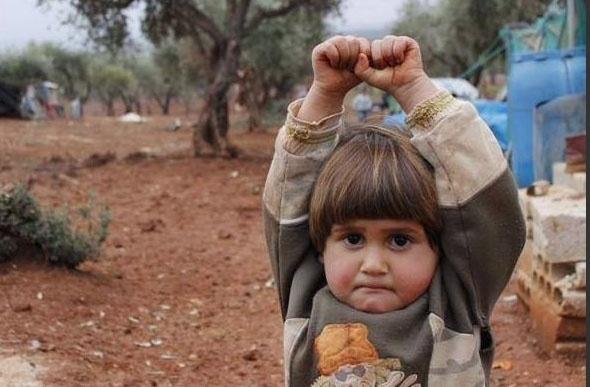 29.mar.2015 - Uma criança síria teria levantado as mãos ao confundir uma câmera fotográfica com uma arma. A imagem foi compartilhada pela fotojornalista Nadia AbuShaban via Twitter e se tornou viral. O autor da foto é o turco Osman Sagirli. A criança é uma menina chamada Hudea, de 4 anos. A imagem foi tirada no campo de refugiados de Atmeh na Síria. Hudea viajou ao campo - a cerca de 10 km da fronteira turca - com a mãe e dois irmãos, a 150 km da cidade deles, Hama