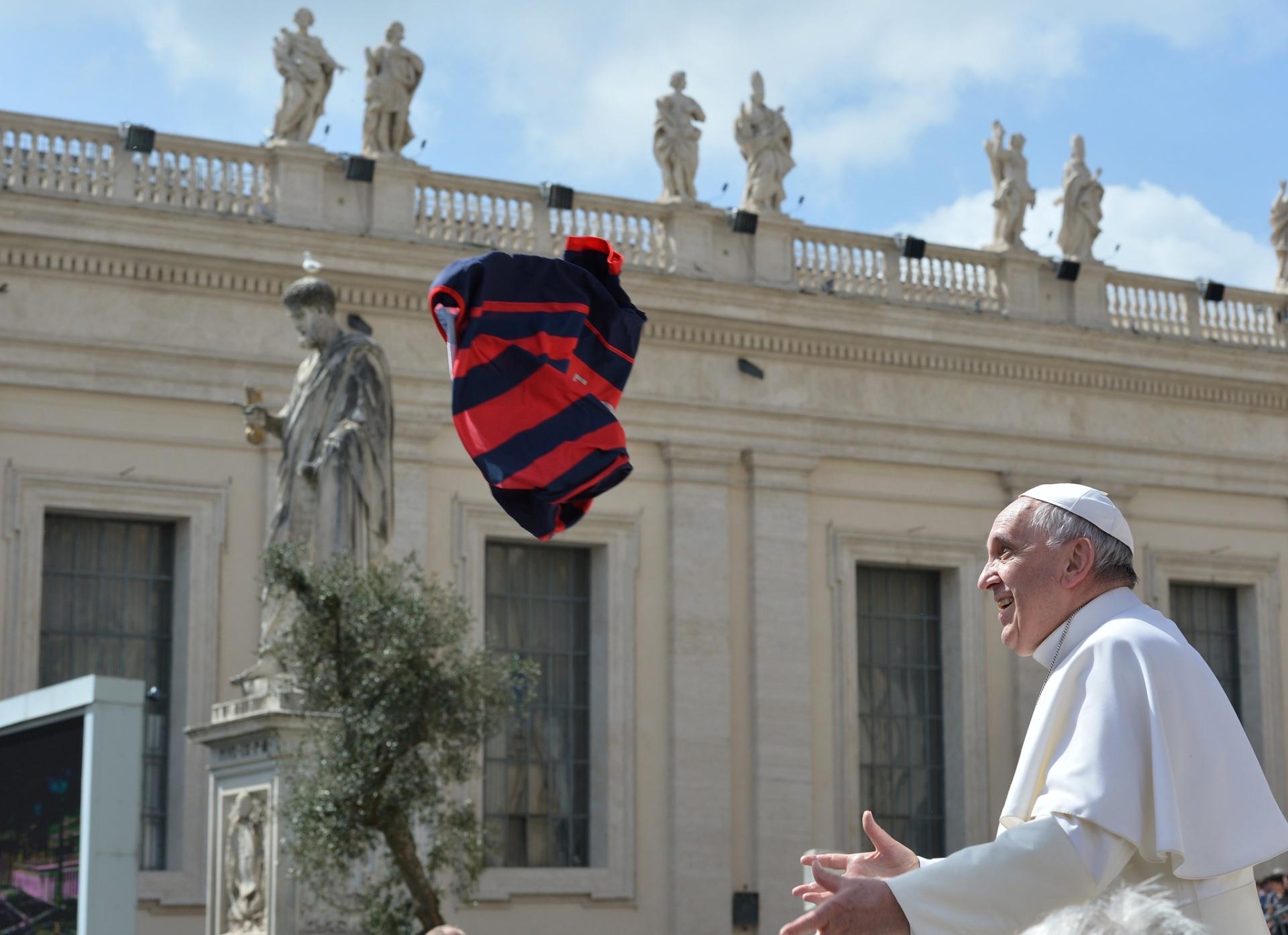 1º.abr.2015 - Papa Francisco se prepara para agarrar uma camisa laçada para ele por um peregrino durante audiência geral semanal na praça de São Pedro, no Vaticano, nesta quarta-feira (1º)