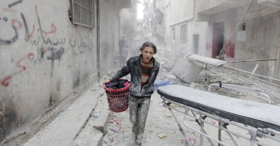 2.abr.2015 - Menino carrega seus pertences de local atingido por uma bomba, que foi lançada pelas forças leais ao ditador sírio Bashar al Assad, no distrito de al-Fardous de Aleppo