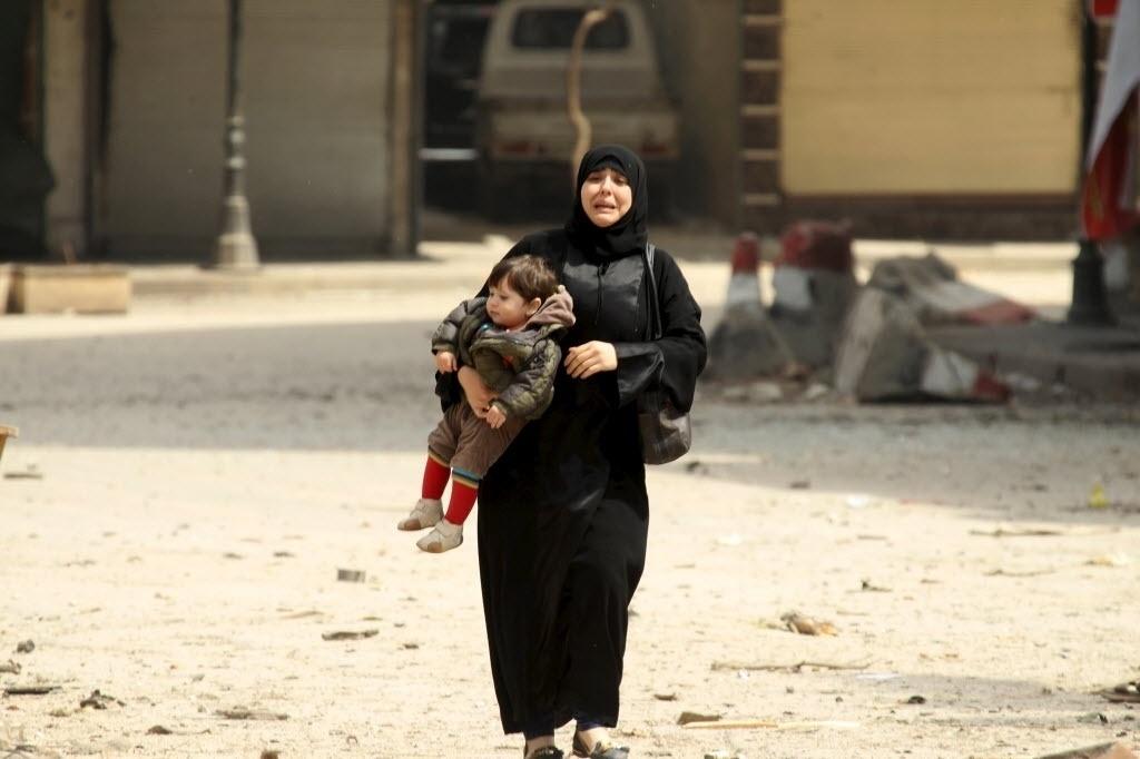 3.abr.2015 - Moradora carregando uma criança chora em local danificado por bombardeios provenientes das forças leais ao ditador da Síria, Bashar al Assad, em Idlib. Uma mesquita foi destruída no ataque, depois que os rebeldes tomaram o controle da área