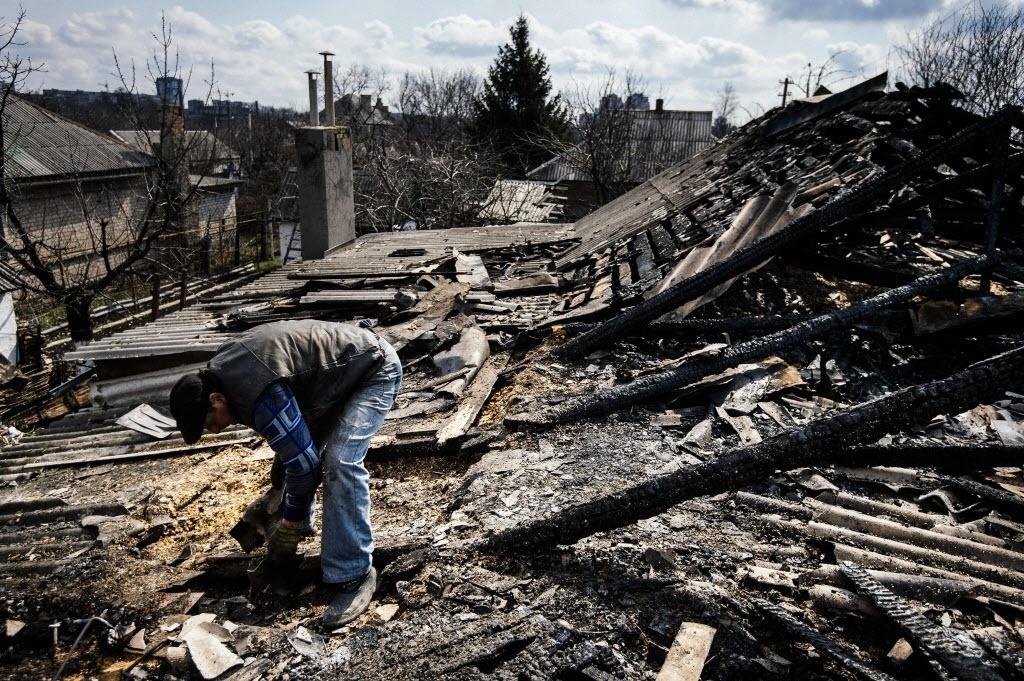 6.abr.2015 - Homem recolhe detritos no telhado após ter a casa queimada devido a um bombardeio na cidade ucraniana de Donetsk oriental nesta segunda-feira (6). No domingo, seis soldados ucranianos foram mortos por minas terrestres em área dominada por separatistas russos, quebrando uma trégua de vários dias em um conflito que começou há um ano