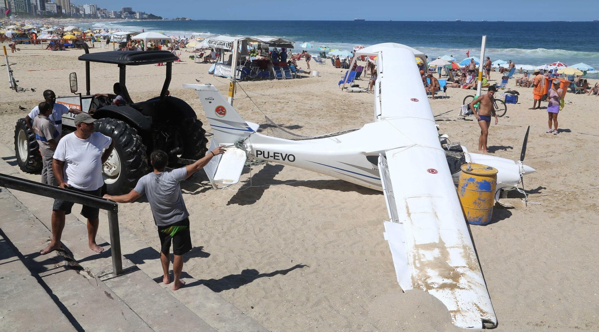 11.abr.2015 - Avião monomotor que caiu no mar nesta sexta-feira a 200 metros da praia do Leblon, na zona sul do Rio de Janeiro, foi removida durante a manhã deste sábado. A aeronave, que tinha dois tripulantes, foi forçada a fazer um pouso de emergência. Os dois tripulantes foram socorridos por pescadores e atendidos por guarda-vidas