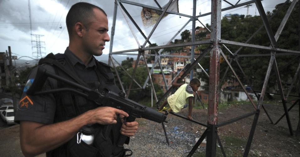 9.abr.2015 - Criança brinca perto de policial no Complexo do Alemão, na zona norte do Rio de Janeiro. No dia 2 de abril, o menino Eduardo de Jesus Ferreira, 10, foi morto por um tiro de fuzil na porta de casa durante uma ação da Polícia Militar